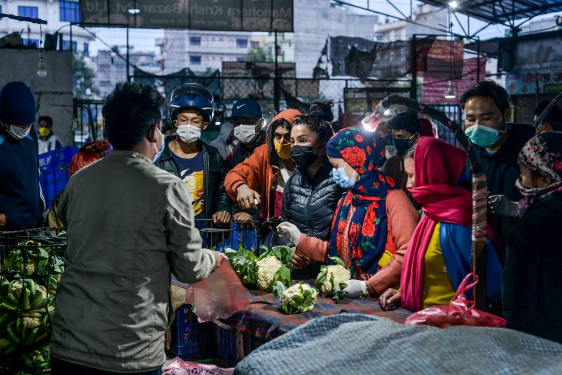Des personnes portant un masque comme mesure préventive contre la COVID-19 sur un marché local à Katmandou, au Népal, le 25 mars 2020.
