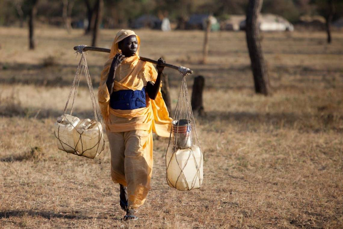 A woman is carrying water in the refugees camp of Jamam, in the Upper Nile State of South-Sudan, on December 14th, 2012.