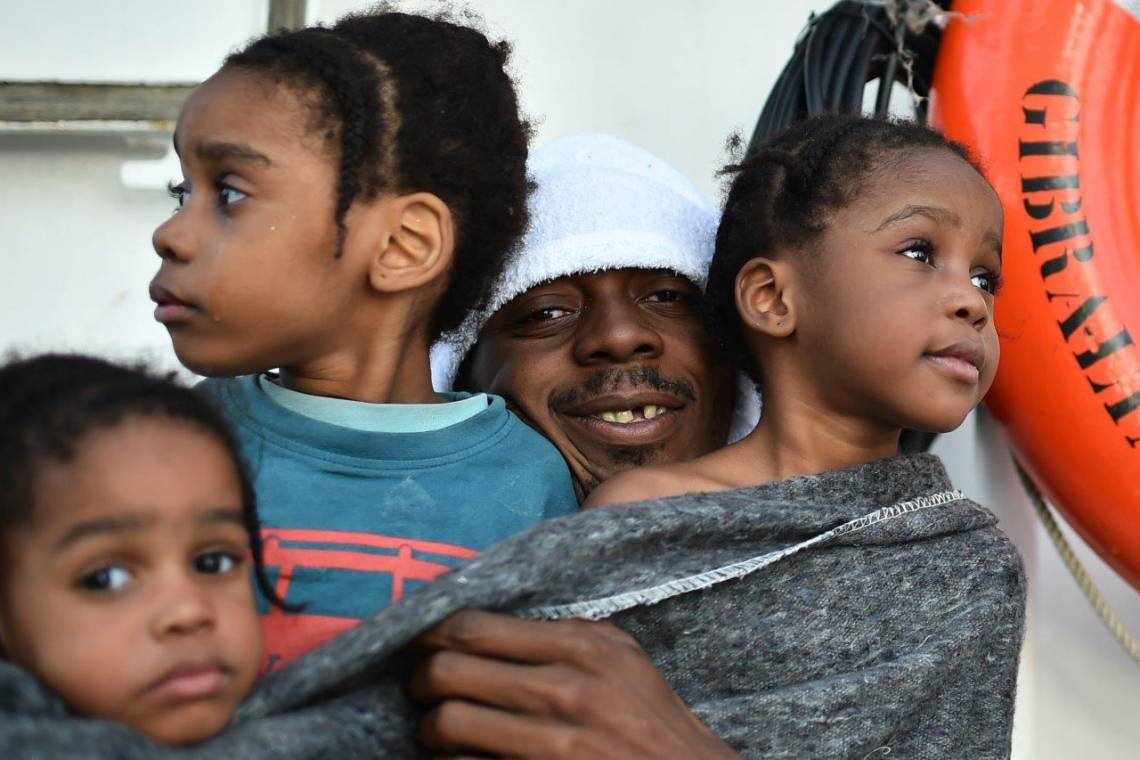 Un père tient ses filles sur le navire de sauvetage de migrants Aquarius en Méditerranée, mai 2016.