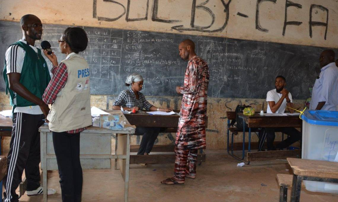 A journalist from Studio Tamani reporting on a polling station in Bamako during the first round of the presidential election in Mali on July 29, 2018.