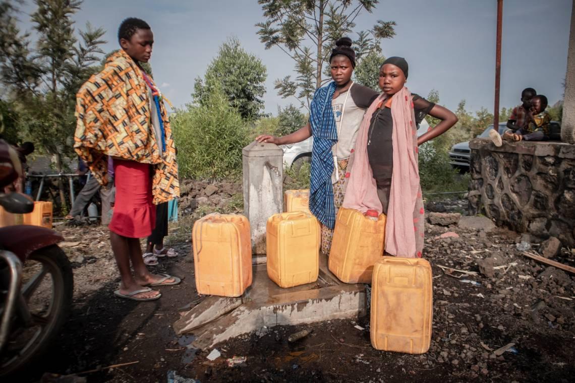 Des enfants font la queue pour obtenir de l'eau distribuée par le gouvernement aux résidents déplacés par l'éruption volcanique du Mont Nyiragongo à Sake, à 25 km au nord-ouest de Goma, le 29 mai 2021.