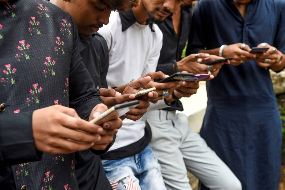 Young eople watch videos on the app TikTok on their mobile phones in Mumbai, India, in November 2019.