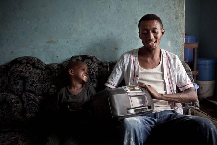 Un père et son fils écoutent la radio à Kinshasa, RDC.