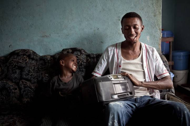 A father and his son listen to the radio in Kinshasa, DRC.
